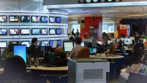 Busy broadcast newsroom with employees and tech