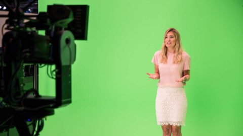 News presenter stands in front of a green screen